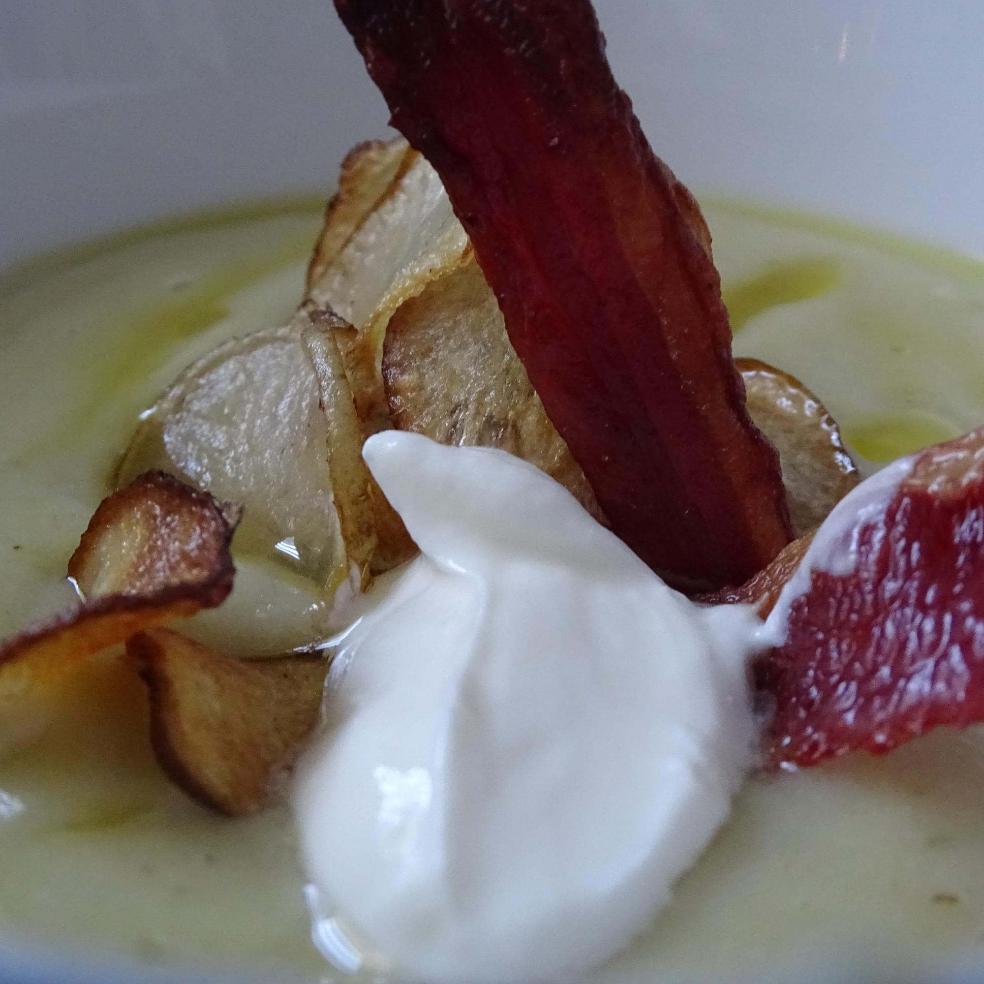 close up of artichoke soup, crispy bacon, greek yogurt