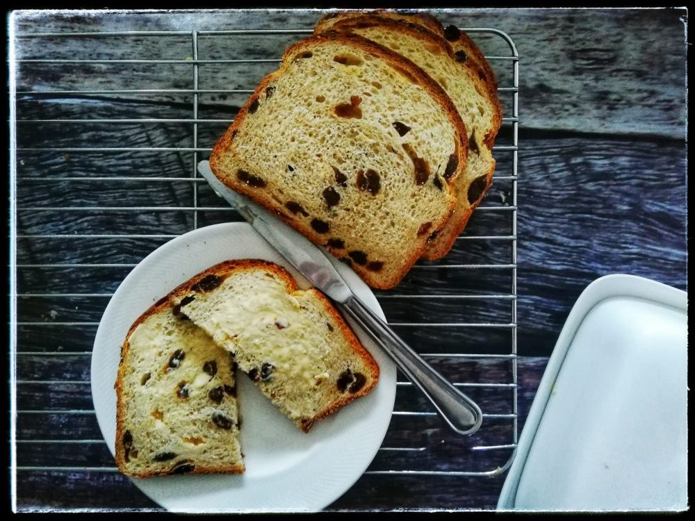 Raisin bread with butter, knife, butter dish