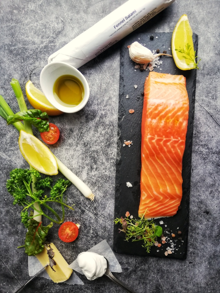 Salmon fillet on slate,parsley sprigs, lemons, fennel salami
