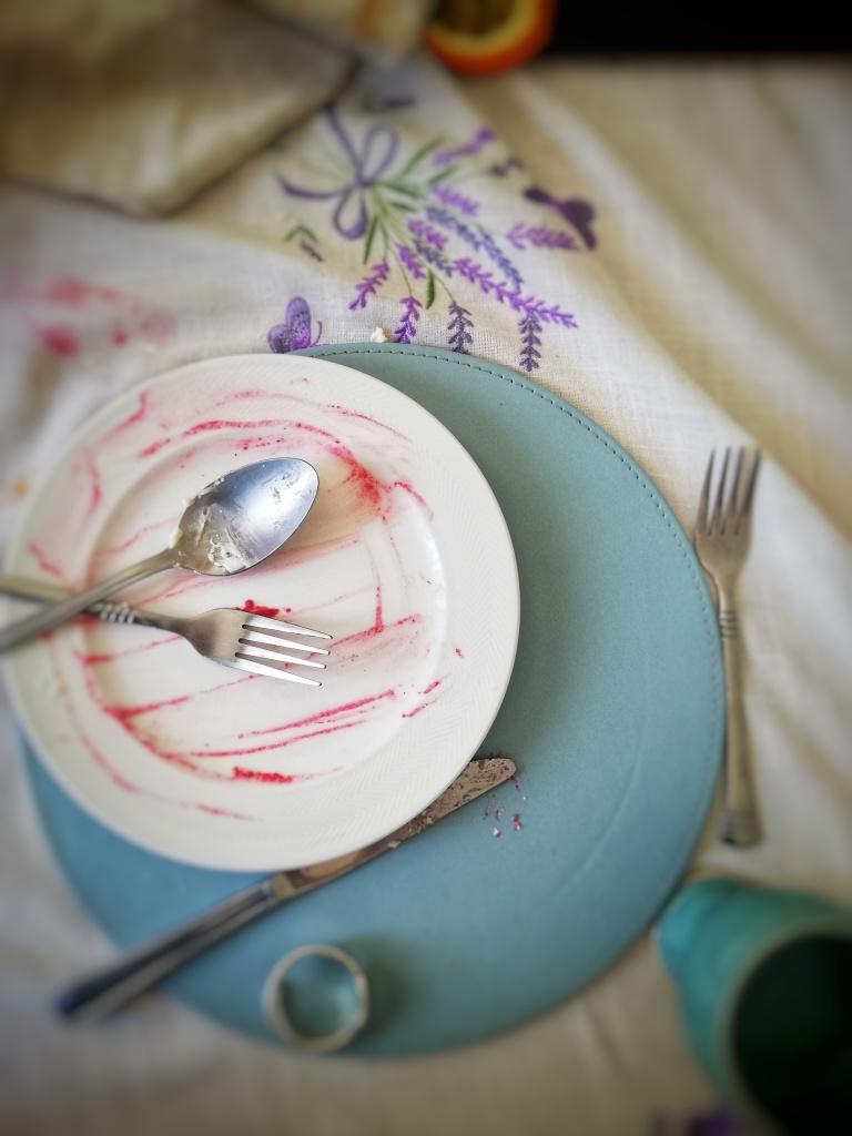 Devoured strawberry and raspberry pavlova, empty plate, cutlery